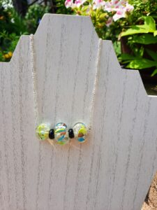 Clear flat multi-color foil glass bead with black spacers on silver chain necklace