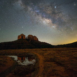 Capture the Milky Way over Sedona, the glow of city lights and the reflection of the Red Rocks in a rain puddle