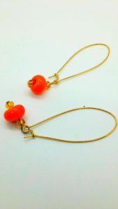Orange glass beads suspended from gold wire earrings